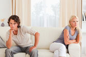 Sorrowful couple sitting on a couch — Stock Photo