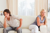 Sorrowful couple sitting on a sofa — Stock Photo