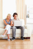 Portrait of an in love couple using a laptop — Stock Photo