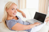Blonde woman switching on her laptop — Stock Photo