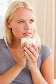 Portret spokojna kobieta siedzi na kanapie przy filiżance kawy — Zdjęcie stockowe