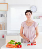 Smiling woman cutting vegetables — Stock Photo