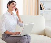 Gorgeous short-haired woman with a laptop and a phone — Stock Photo