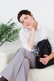 Short-haired bored businesswoman sitting on a sofa — Stock Photo
