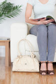 Part of a Woman on a sofa with a bag and a magazine — Stock Photo