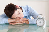 Sleeping woman with her head on the desk next to an alarmclock — Stock Photo
