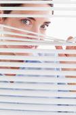 Beautiful brunette businesswoman peeking through a venetian blin — Stock Photo