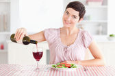 Woman pouring redwine in a glass — Stock Photo