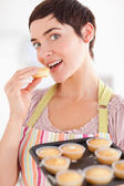 Charming brunette woman showing muffins while eating one — Stock Photo