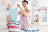 Smiling Woman folding clothes — Stock Photo