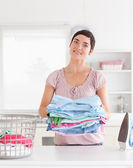Charming Woman with a pile of clothes — Stock Photo