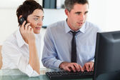 Businesswoman telephoning while her colleague is using a compute — Stock Photo