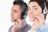 Close up of workers speaking through headsets — Foto Stock