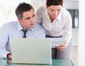 Colleagues comparing a blueprint folder to an electronic one — Stock Photo