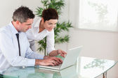 Zakenvrouw wijzend op iets aan haar collega op een laptop — Stockfoto