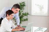 Manager and his secretary working with a laptop — Stock Photo
