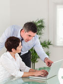 Portrait of a manager pointing at something to his secretary on — Stock Photo