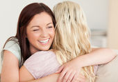 Joyful women hugging on a sofa — Stock Photo
