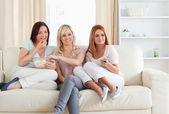 Laughing Women watching a movie eating popcorn — Stock Photo