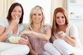 Laughing young Women watching a movie eating popcorn — Stock Photo