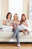 Glada vänner på en soffa titta på en film — Stockfoto