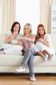Joyful Friends lounging on a sofa watching a movie — Stockfoto