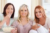 Uśmiechnięty znajomych wyleguje się na kanapie oglądając film — Zdjęcie stockowe