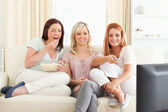 Nádherné ženy, lenošení na pohovce, sledovat film — Stock fotografie