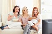 Wspaniałe kobiety wyleguje się na kanapie oglądając film — Zdjęcie stockowe