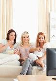 Młode kobiety, wyleguje się na kanapie oglądając film — Zdjęcie stockowe