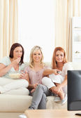 Young women lounging on a sofa watching a movie — Stok fotoğraf