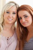 Kobiety uśmiechający się wyleguje się na kanapie — Zdjęcie stockowe