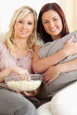 Smiling women lounging on a sofa watching a movie — 图库照片