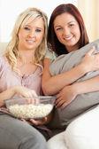 Uśmiechający się wyleguje się na kanapie oglądając film kobiety — Zdjęcie stockowe
