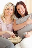 Glada kvinnor att ligga på en soffa titta på en film — Stockfoto