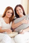Sorridentes jovens mulheres descansando em um sofá assistindo a um filme — Foto Stock