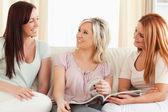 Słodkie kobiety wyleguje się na kanapie z magazynu — Zdjęcie stockowe