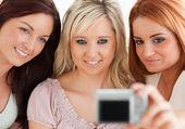 Charmiga kvinnor att ligga på en soffa med en kamera — Stockfoto
