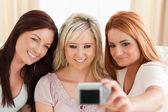улыбающиеся женщины, развалившись на диване с камерой — Стоковое фото