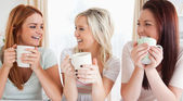 Young Women sitting at a table with cups — Stock Photo