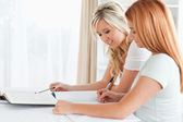 Cooperating Women sitting at a table doing their homework — Stock Photo