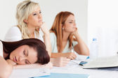 Bored university students one sleeping sitting at a table — Stock Photo