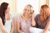 Cheerful friends sitting on a sofa — Stock Photo