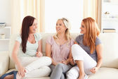 Cheering friends lounging on a sofa — Stock Photo
