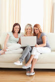 Cute women relaxing on a sofa with a laptop — Zdjęcie stockowe