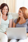 Laughing Women sitting on a sofa with a laptop and a phone — Stock Photo