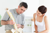 Chiropractor and patient looking at a model of a spine — Stock Photo