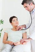 Doctor examining a female patient — Stock Photo