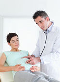Doctor listening into the belly with a stethoscope — Foto de Stock