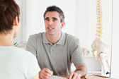 Doctor and patient sitting at a table talking — Stock Photo